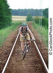 Biker riding on railway track