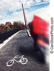 biker roadsign on the grey asphalt of a bridge
