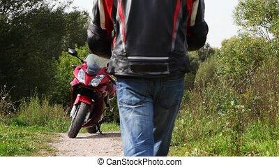 Biker sit down on motorcycle and close visor on it helmet