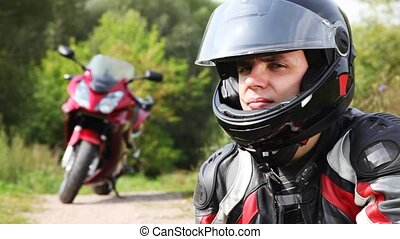Biker sits near motorcycle, see and close visor on it helmet