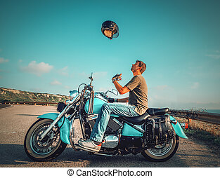 Biker sitting on a classic motorcycle tossing the helmet