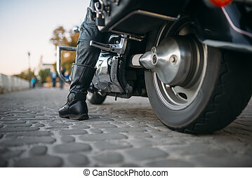 Biker sitting on motorcycle, back view from ground