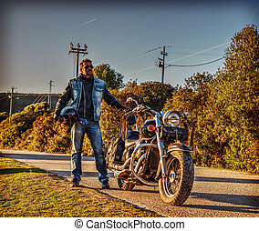 Biker standing by a classic motorcycle
