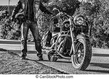 Biker standing by a classic motorcycle in black and white