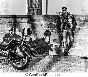 Biker standing by a classic motorycle in b&w