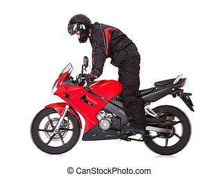 Biker standing up while riding his motorbike