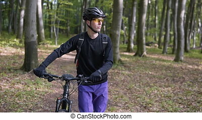 Biker Walks Forest with Bike - Young backpacked sports man...