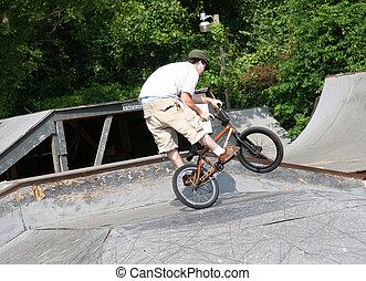 Biker Wheel Standing - BMX biker doing tricks at skate park....