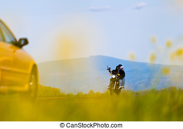 Biker with a passenger traveling towards yellow car