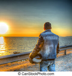 Biker with helmet looking at the sun at sunset