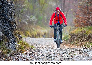 Biker with mountain bike downhill on dirt road