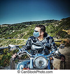 biker with virus protection mask on a classic motorcycle