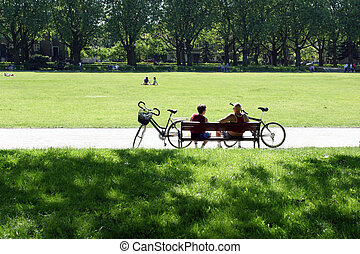 Bikers sitting on a bench in the park in summer