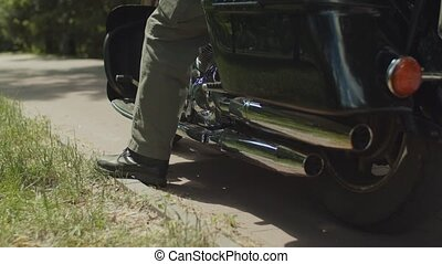 Bikers foot in boots sitting on motorcycle - Low section of...