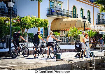 Bikers keep the bikes and walking in Puerto De Mogan on Gran Canaria island.