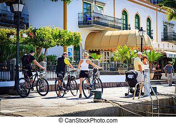 Bikers keep the bikes and walking in Puerto De Mogan on Gran Canaria island.