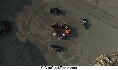 Bikers ride around group of womans aerial top view shot