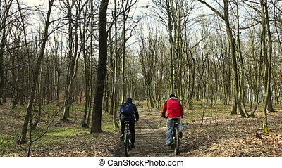 bikers ride in spring forest