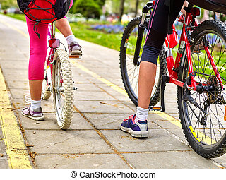 Bikes bicyclist girl. Children feet and bicycle wheel. Low ...
