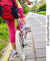 Bikes bicyclist girl. Children feet and bicycle wheel. Low section.