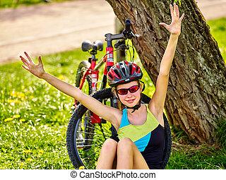 Bikes child wearing helmet. Girl in cycling sitting near ...