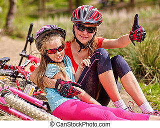 Bikes cycling family. Happy mother and daughter are sitting on road near bicycles.