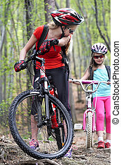 Bikes cycling family. Mother and daughter wearing helmet are cycling on bicycles .