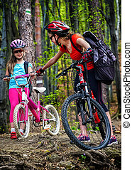 Bikes cycling family. Mother and daughter wearing helmet cycling bicycles.