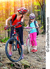 Bikes cycling family. Mother and daughter wearing helmet cycling bicycles .