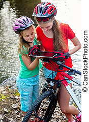 Bikes cycling girl. Children rides bicycle. Bicyclist watch tablet computer.