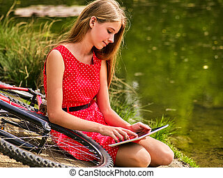 Bikes cycling girl into park. Children watch tablet pc.