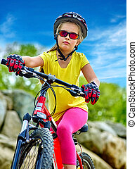 Bikes cycling girl into park rides bicycle on mountains.
