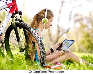 Bikes cycling girl wearing headset watch in pc tablet near...