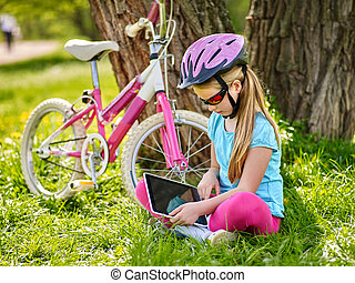 Bikes cycling girl wearing helmet in cycling sitting near bicycle and watch pc tablet.