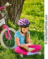 Bikes cycling girl wearing helmet reads book.