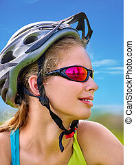 Bikes cycling girl wearing helmet rides bicycle aganist blue sky.