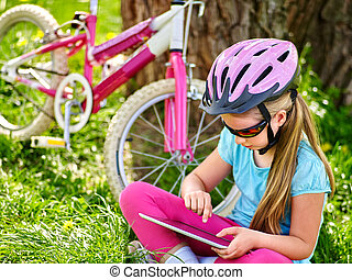 Bikes cycling girl wearing helmet watching at tablet pc .