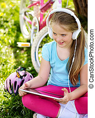 Bikes cycling girl wearing helmet watching at tablet pc in cycling.