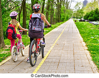 Bikes cycling girls with rucksack cycling on bike lane. -...