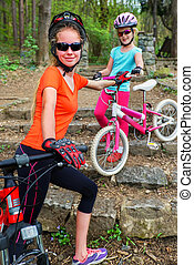 Bikes family. Mother and daughter wearing helmet cycling on bicycles .
