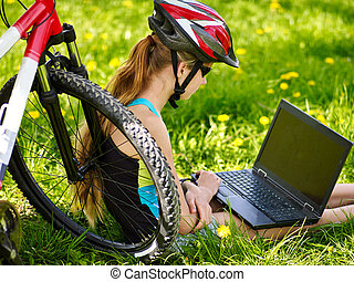 Bikes girl in cycling helmet sitting near bicycle with laptop.