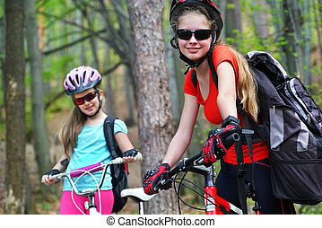 Bikes girls. Happy family wearing helmet are cycling on bicycles .