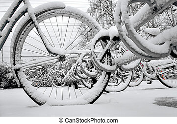 Bikes in rack in winter - Close up of wheel of bike in...