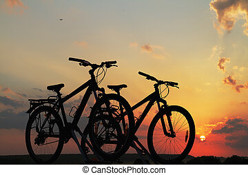 Bikes on top of a car against sunse
