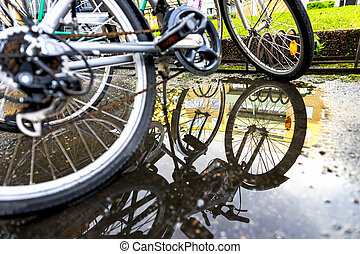 bikes with reflection - Focus on reflection in puddle with...
