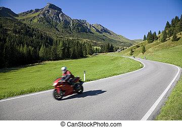Speedy motorbike on mountain road - Dolomites, Italy.