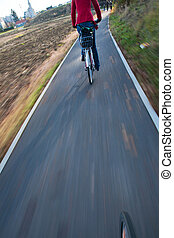 biking, -, jonge vrouw , biking, te werken, (the, beeld, is, motie, vaag, om te, overbrengen, movement;, brandpunt, is, op, de, wiel, de, vrouwlijk, fietser, is, uit weggegaan, van, focus)