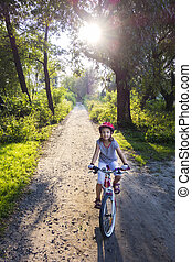 Biking sunset - Girl on a bicycle in summer park outdoors, ...