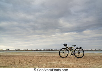 spring biking, touring or commuting - bicycle on a lake beach, Boyd Lake State Park in northern Colorado