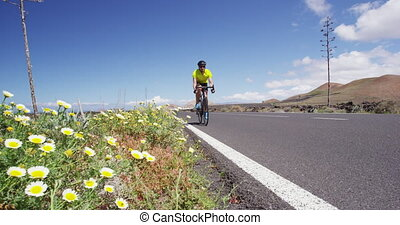 Biking tourist man cycling on road bike traveling in summer doing ecotourism. Sports athlete cyclist riding bicycle for fitness in summer holidays. SLOW MOTION RED EPIC.
